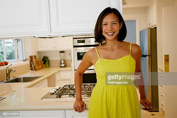 Mixed race woman smiling in kitchen