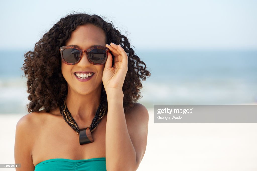 Mixed race woman smiling on beach : Stock Photo
