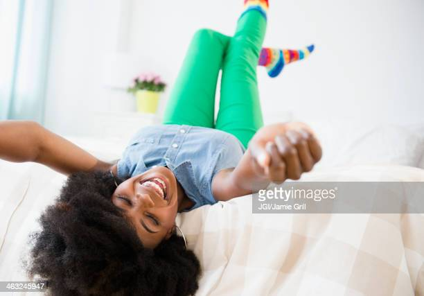 Mixed race woman smiling on bed
