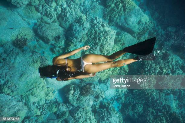 Mixed race woman snorkeling near tropical reef