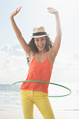 Mixed race woman spinning plastic ring on beach