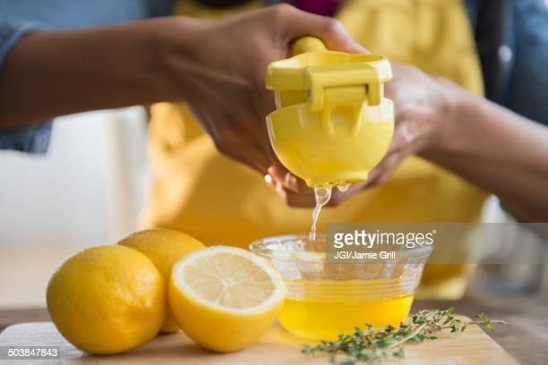 Mixed race woman squeezing lemons