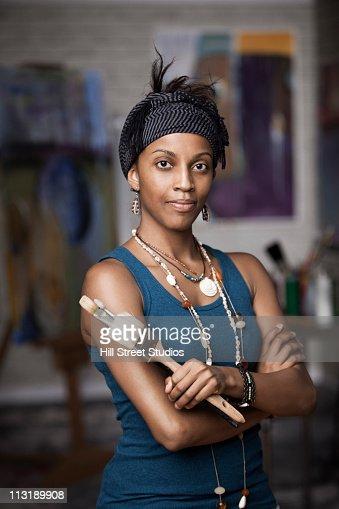 Mixed race woman standing in artist's studio