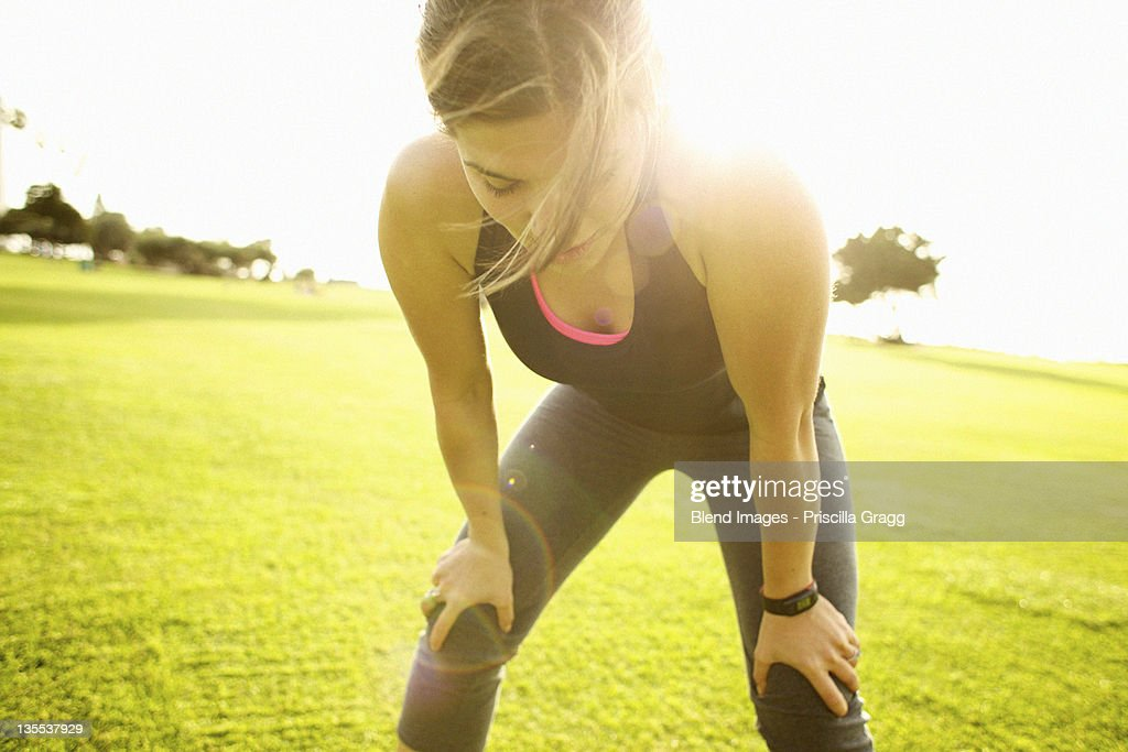 Mixed race woman standing in field after exercise : Stock Photo