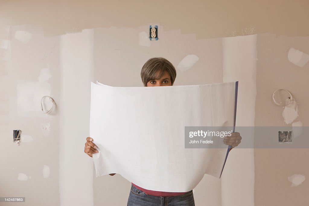 Mixed race woman standing in unfinished room with blueprints : Stock Photo