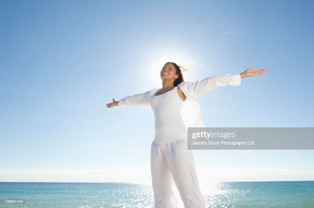 Mixed race woman standing near ocean with arms outstretched : Stock Photo