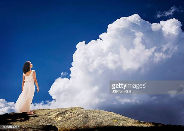 Mixed race woman standing on mountaintop