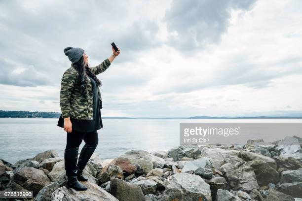Mixed Race woman standing on rocks at ocean posing for cell phone selfie
