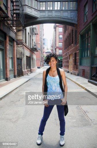 Mixed race woman standing on urban street : Stock Photo