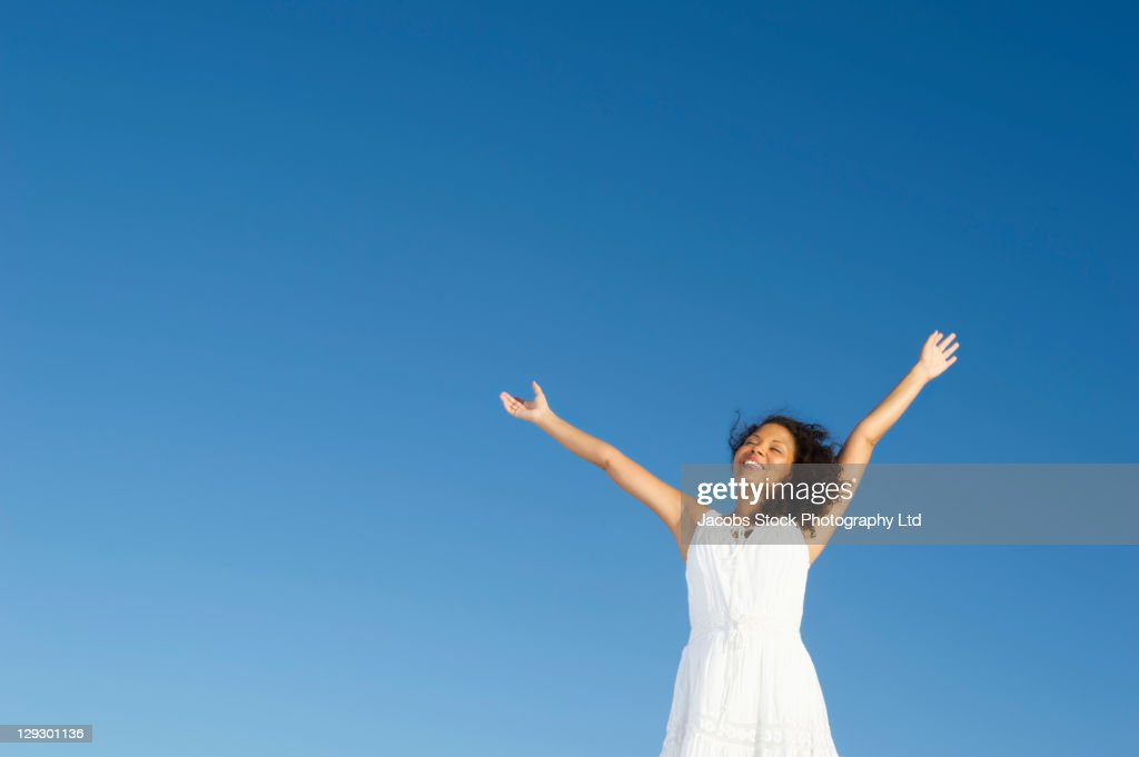 Mixed race woman standing outdoors with arms raised : Stock Photo