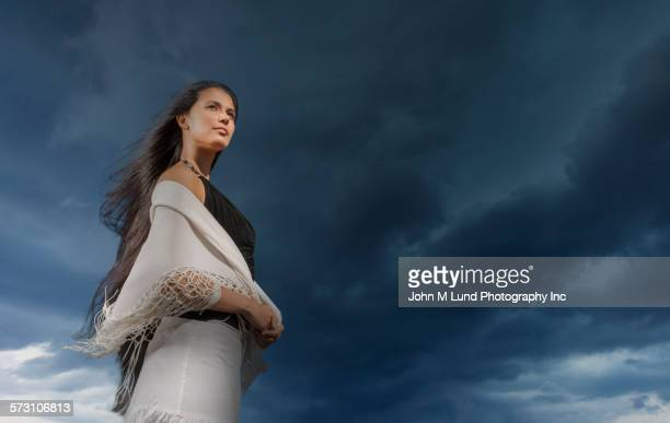 Mixed race woman standing under stormy sky