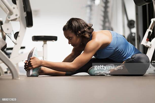 Mixed Race woman stretching legs on floor at gymnasium