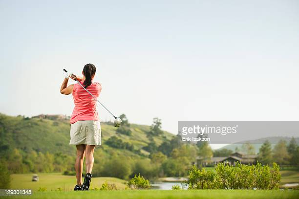 Mixed race woman swinging golf club on golf course