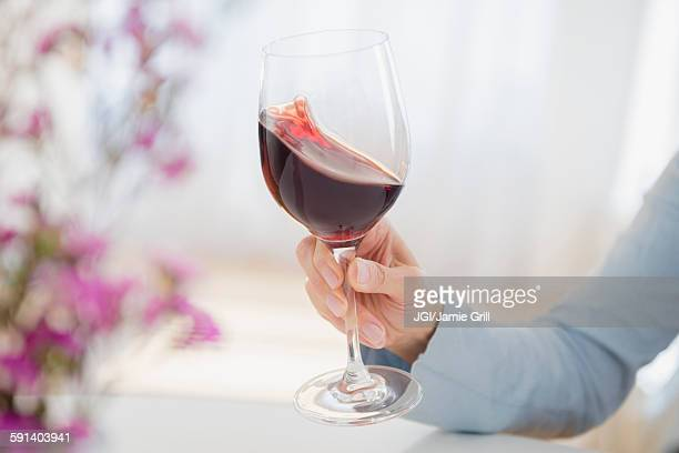 Mixed race woman swirling glass of wine