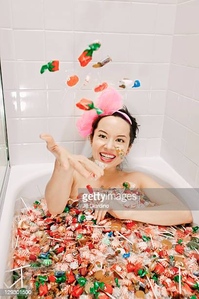 Mixed race woman taking a bath in candy