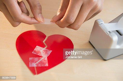Mixed race woman taking broken paper heart : Stock Photo