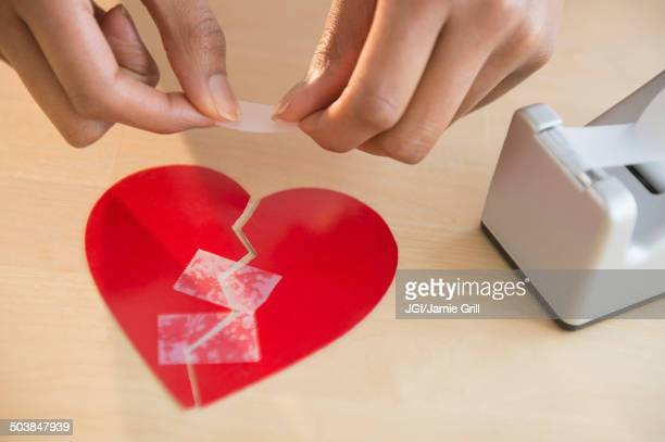Mixed race woman taking broken paper heart