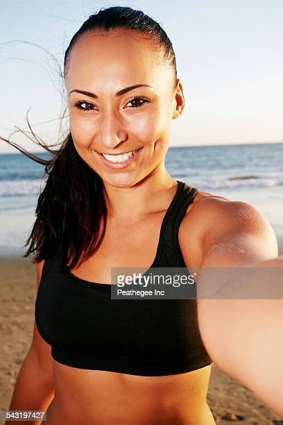 Mixed race woman taking cell phone selfie on beach