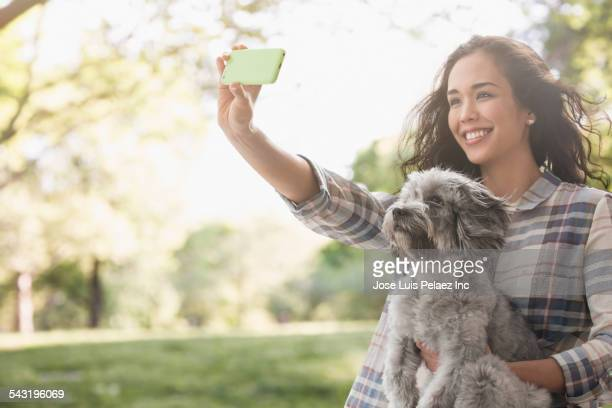 Mixed race woman taking photograph with dog in park