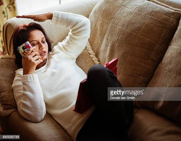 Mixed race woman talking on cell phone and using digital tablet