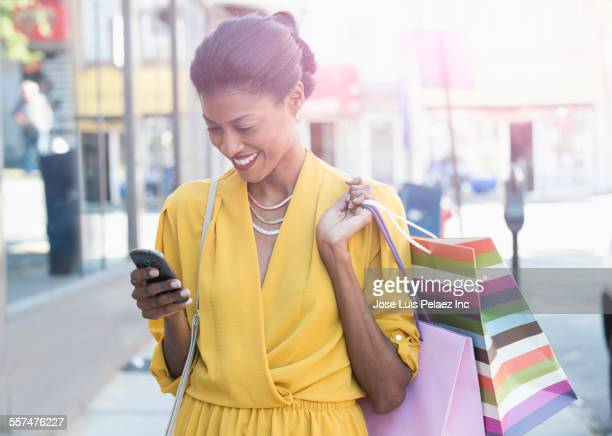 Mixed race woman texting on cell phone holding shopping bags