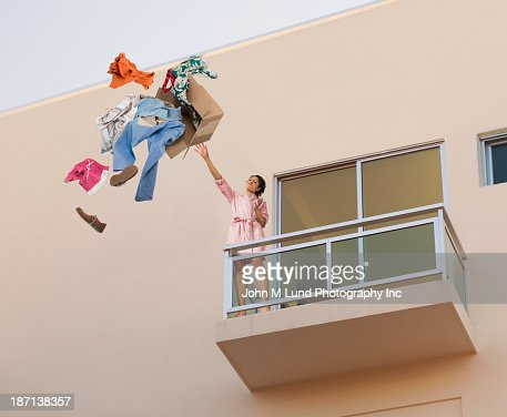 Mixed race woman throwing clothes off balcony