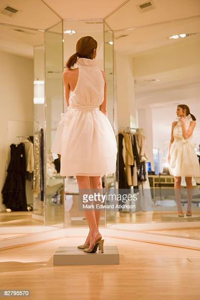 Mixed race woman trying on dress in shop