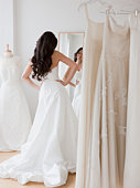 Mixed race woman trying on wedding dresses