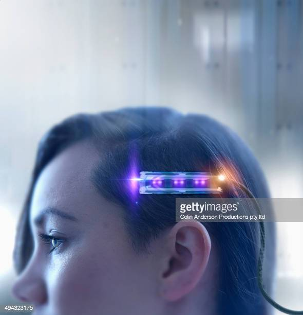 Mixed race woman undergoing futuristic brain scan