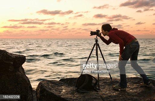 Mixed race woman using camera near ocean