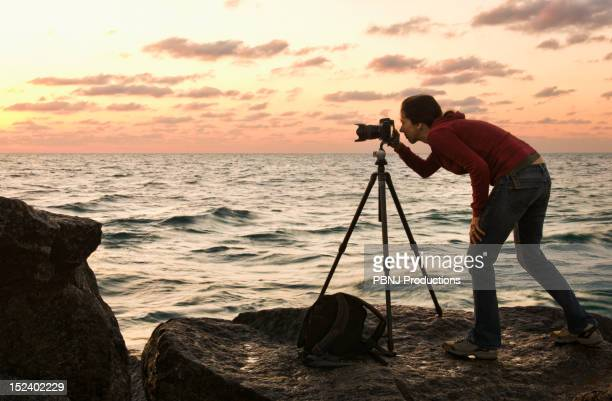 Mixed race woman using camera near ocean