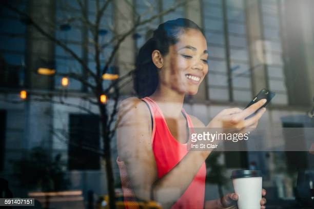 Mixed race woman using cell phone in cafe