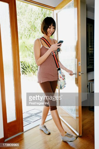 Mixed race woman using cell phone in doorway