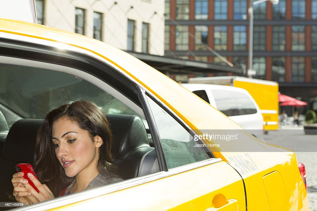 Mixed race woman using cell phone in taxi