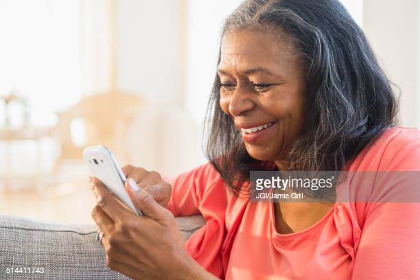 Mixed race woman using cell phone on sofa