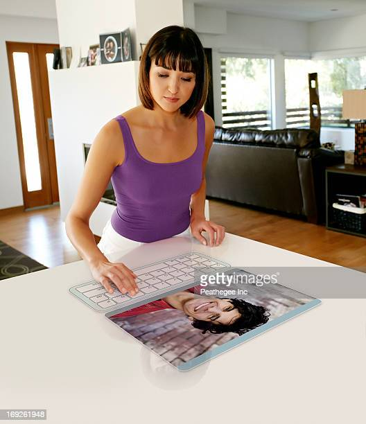 Mixed race woman using computer in table