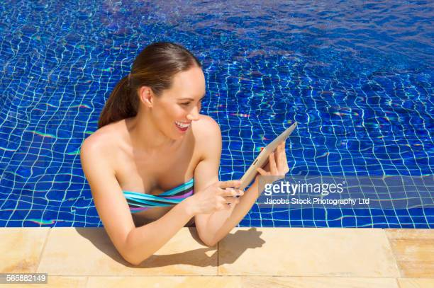 Mixed race woman using digital tablet in swimming pool