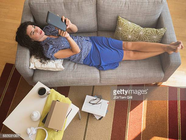 Mixed race woman using digital tablet on sofa