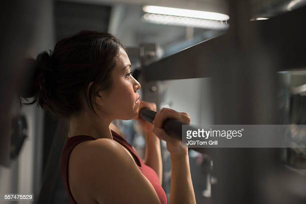 Mixed race woman using exercise machine in gym