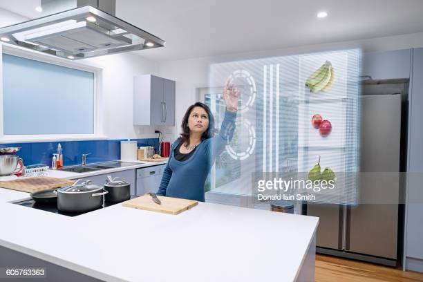 Mixed race woman using holographic screen in kitchen
