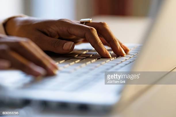 Mixed race woman using laptop at desk