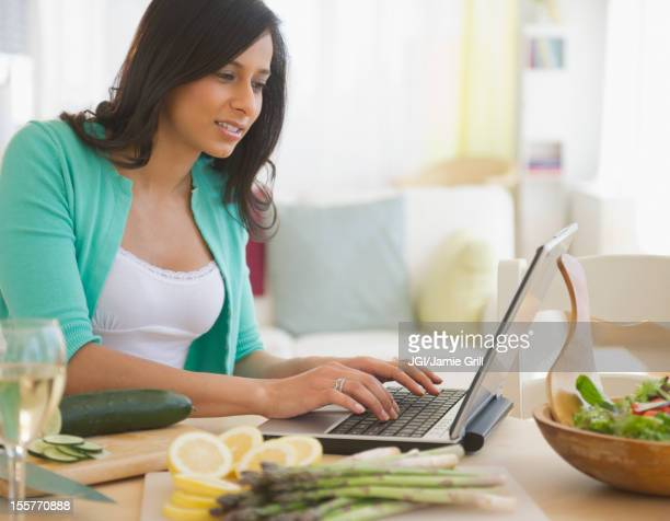 Mixed race woman using laptop in kitchen