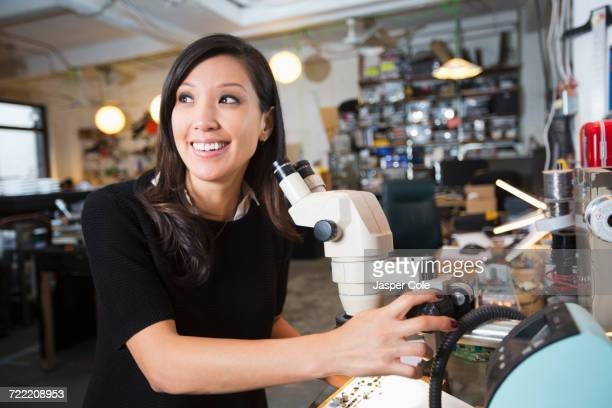 Mixed Race woman using microscope