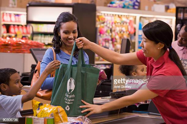 Mixed race woman using reusable bag in grocery store