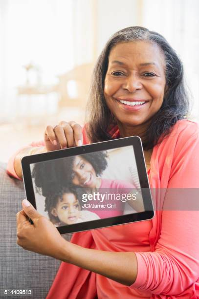 Mixed race woman using tablet computer on sofa