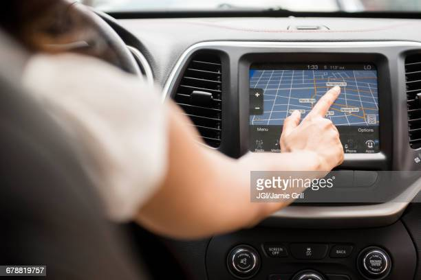 Mixed Race woman using touch screen navigation map in car