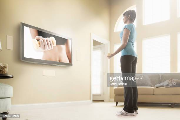 Mixed race woman watching exercise program on television