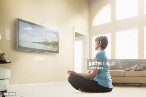 Mixed race woman watching meditation program on television