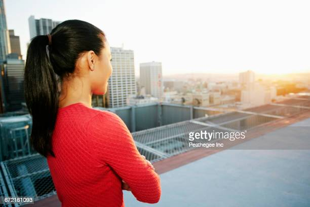 Mixed Race woman watching sunset on urban rooftop