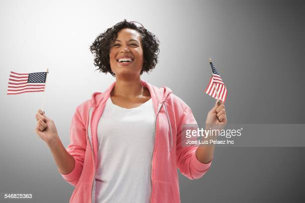 Mixed race woman waving American flags